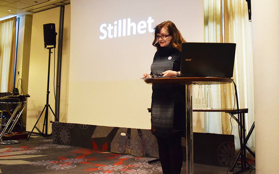 """Foto av Åshild Kjelsnes, som opnar nasjonal rassikringskonferanse 2017. På skjermen bak ho står det """"Stillheit"""" med kvite bokstavar på svart bakgrunn."""