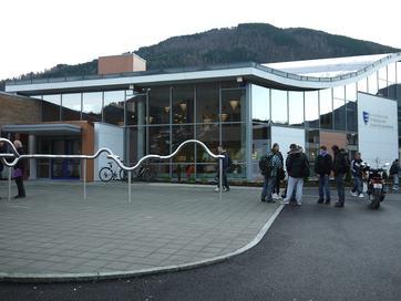 eksteriørt bilde av sogndal vidaregåande skule skugge, nokre elevar står foran inngangspartiet, skilt på vegg seier Sogndal vidaregåande skule og syner fylkesvåpenet