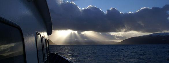 Foto som syner utsikt frå ein båt som er til sjøs. Det er i skumringa, og sola bryt gjennom skyene. Vi ser litt av båten til venstre i bilete og fjell i horisonten.