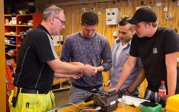 Foto som syner ein lærar og tre elevar som står rundt eit apparat i ein verkstad. Læraren viser fram noko og forklarer, elevane følgjer med.