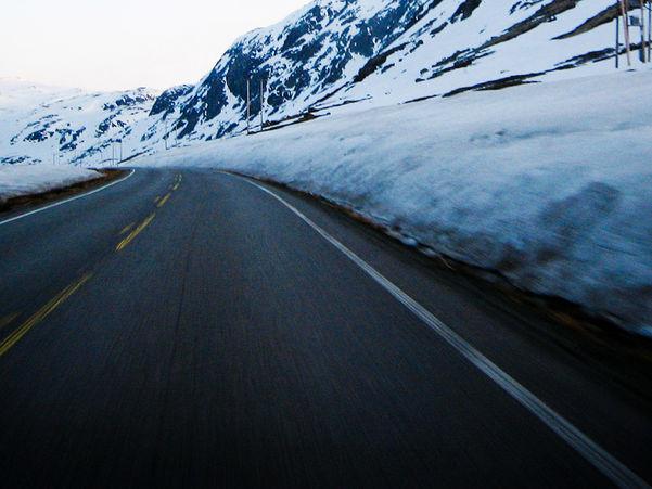 Foto frå vegen over Hemsedalsfjellet. Vegen er berre, men det ligg snø i terrenget.