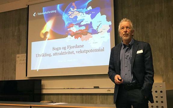 Foto av forskar Knut Vareide  i Telemarksforsking som presenterer Regional analyse for Sogn og Fjordane 2016. Vareide står framfor power point-presentasjonen.