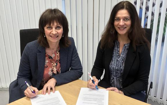 fylkesordførar Jenny Følling og fylkesmann Anne Karin Hamre sit ved eit bord og smiler til kameraet, inne, med pennar i hendene og to signerte dokument foran seg på bordet.