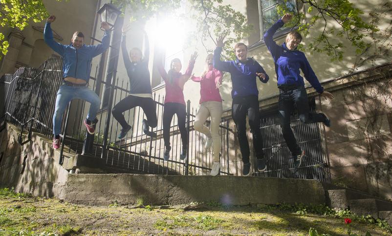 Smilande ungdommar som hoppar opp i lufta med hendene i veret