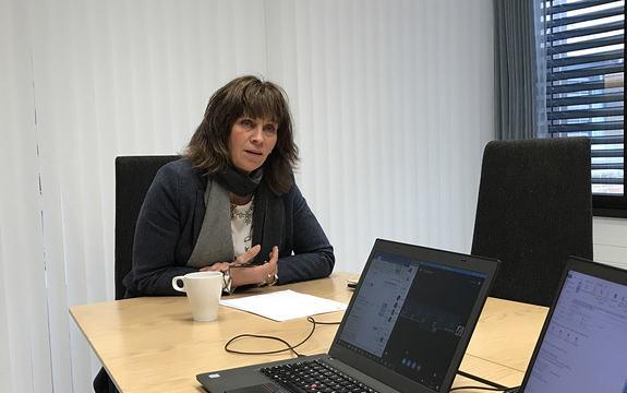 Foto av fylkesordførar Jenny Følling ved eit møtebord. Ho har på seg blå jakke og grått skjerf. På bordet framføre seg har ho ein kaffikopp og eit papir. I framkant i biletet ser vi to pc-ar.