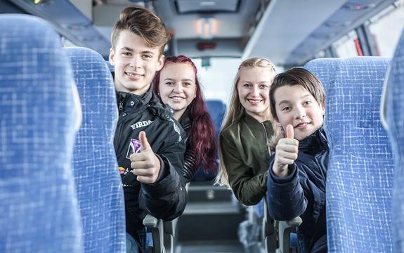 Foto av fire ungdomar i ein buss. Det sit to på kvar side av midtgangen, to jenter og to gutar. Gutane sit fremst og viser tommel opp.