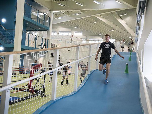 Foto frå Bevægelseshuset Spiralen i den danske byen Kalundborg. Det syner ein ung mann som spring i ei joggeløype med humpar. Til venstre litt bak han ser vi ein boksering og folk som driv med andre aktivitetar.