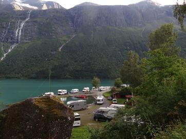 Oversiktsbilete frå Sande Camping i Lodalen. Biletet er teke ned mot vatnet, og vi ser både campingbilar, campingvogner, vanlege bilar og hytter. Lovatnet i høge fjell i bakgrunnen.