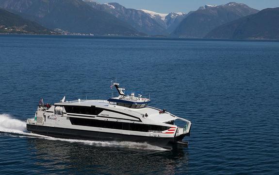 Foto av hurtigbåten MS Vingtor i fart på fjorden. Det er sommar, og vi ser bebyggelse i det fjerne.