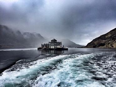 Foto av eit oppdrettsanlegg som ligg ute på sjøen. Vêret er grått, og skyene heng nedover fjellsidene i bakgrunnen.
