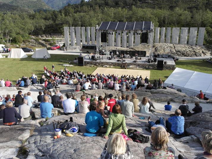 totalbilde av gulatinget også kalla tusenårsstaden, publikum sit foran steinrekka og artistar på ei scene foran denne. sommar og sol.