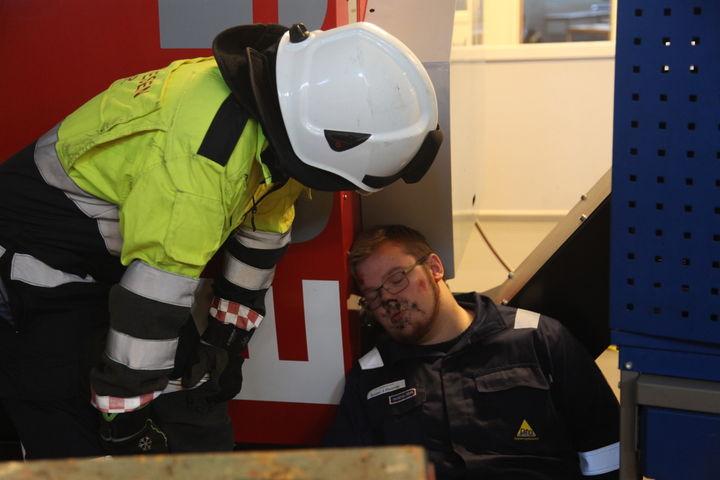 Ein elev sit på golvet og latar som han er skadd mens redningspersonell undersøkjer