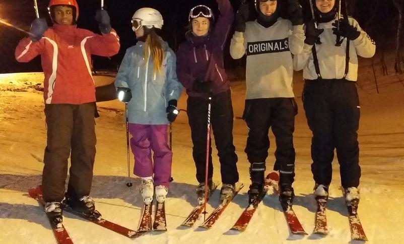 Elevar som står på ski.