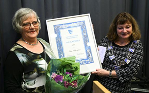 Kari Støfringsdal tek imot diplom, blomar og ein sjekk frå fylkesordførar Åshild Kjelsnes.