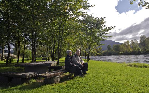To eldre sit i ein park ved ei elv.