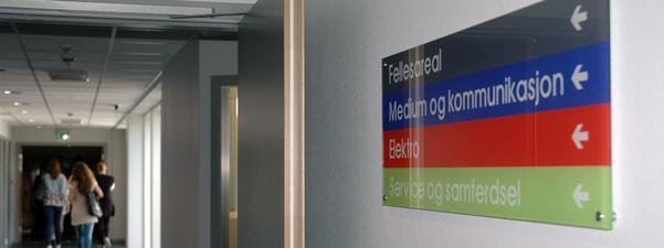 Gang med skilt til fellesareal, medium og kommunikasjon, elektro og service og samferdsel.