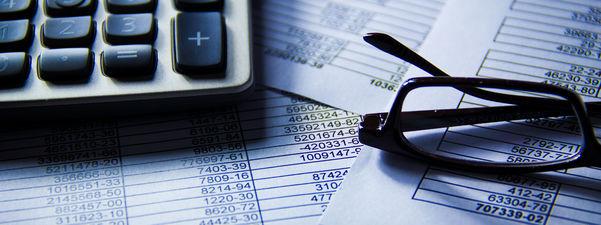 Illustrasjon av verksemda til kontrollutvalet, kalkulator og briller ligg oppå papir med mykje tal. Foto: Ken Teegardin