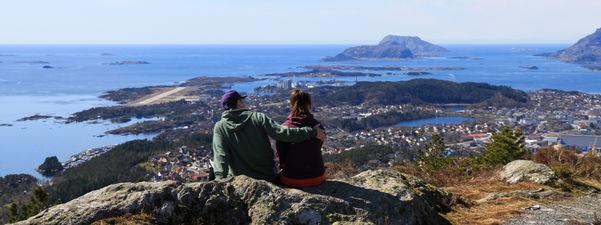 To ungdomar (ei jente og ein gut) sit på ein topp og ser utover Florø og mot storhavet. Begge har hettegenser, han har ein cap på hovudet og held armen rundt ho. Foto: Truls Kleiven