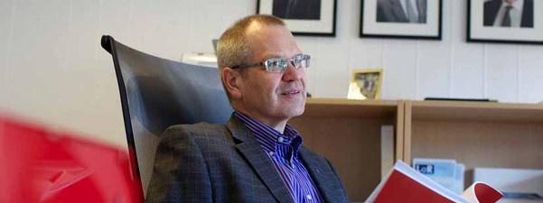 Fylkesrådmann Tore Eriksen på kontoret sitt. Han har på seg blå- og kvitstripete skjorte og grå dressjakke. Han ser ut i lufta, men har framfor seg eit raudt hefte. Foto: Oskar Andersen