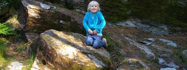 Brage Solberg Losnegård sit på ein stein i Kvernsteinsparken på Hyllestad. Foto: Sigrid Solberg.