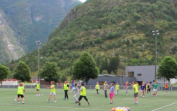 Ungdomar spelar fotball på kunstgrasbana i Lærdal. Det eine laget har gule vestar, det andre har vanlege t-skjorter. Det er sommar og grønt på trea og på fjella i bakgrunnen. Foto: Guro Høyvik