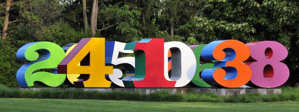 Foto av store, fargerike tal som står på ein grøn plen med ein skog i bakgrunnen. Vi ser tala to, fire, fem, ein, null, tre og åtte. Dei er grøne, gule, raude, kvite, oransje og lilla. Foto: Serge Melki, www.flickr.com