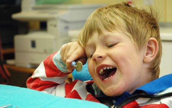 Foto av ein femåring i tannlegestolen med noko tannlegeutstyr framfor seg. Han gliser og speglar seg i den vesle runde spegelen tannlegen brukar til å sjå inni munnen.
