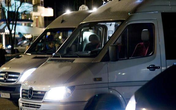Foto av to maxi-taxiar stilte opp utanfor Sunnfjord Hotel i Førde ei natt. Det er mørkt ute, men vi skimtar hotellet i bakgrunnen.