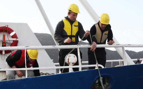 """Foto som syner tre elevar på opplæringsfartøyet """"Skulebas"""" Dei tre har redningsvestar og gule hjelmar. Foto: Måløy vidaregåande skule"""