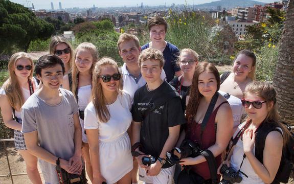 Foto av elevane i ungdomsbedrifta RAW Media UB ved Hafstad vidaregåande skule. Biletet er frå ein studietur til Frankrike, og elevane er samla på ein topp over byen dei besøker. Fleire av elevane har speglreflekskamera i hendene.