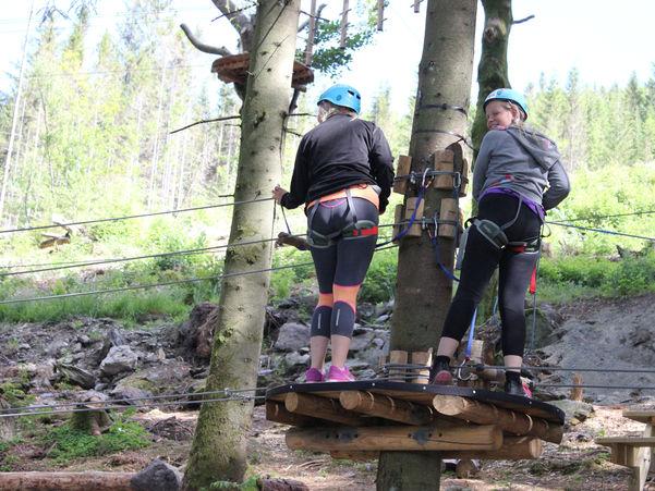 Foto som syner to unge jenter i ein klatrepark. Dei er sikra med selar og wirar, og har på seg hjelm. Dei står på ei plattform som eg bygd litt oppe i eit tre. Foto: 4H Rogaland/www.flickr.com.