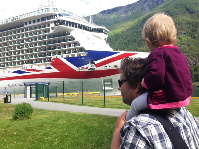 Foto som syner cruiseskipet Britannia til kai i Flåm. I framgrunnen i biletet ser vi ein mann med ein liten unge på skuldrene, som begge ser mot det store skipet. Foto: Birthe Johanne Finstad/Sogn og Fjordane fylkeskommune