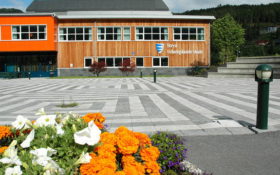 foto av Stryn vidaregåande skule, sett utanifrå, hovudinngang med blomar i forgrunnen, sommar