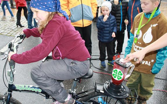 """Jente med blått skaut og burgunderraud gensar syklar på """"smoothiesykkelen"""" - ein sykkel som gjer at ein blender på baksetet lagar smoothies når ein syklar. Foto: Åge Avedal"""