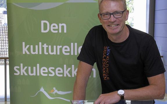 Øyvind Høstaker, koordinator i Den Kulturelle Skulesekken (DKS) står smilande framfor ein reklameplakat/rollup for DKS. Foto.