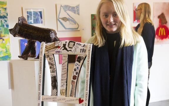 Foto av 16-årige Jenny Hatlelid Holsæter på kunstutstillinga under UKM-fylkesmønstringa i Førdehuset i april 2015.