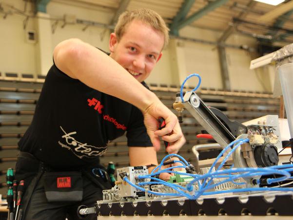 Bilete som syner ein elev eller lærling som skrur ledningar medan han ser i kameraet og smiler. Foto: WorldSkills Norway