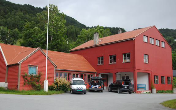 Foto av det raude Hennebygda samfunnshus. Det står tre bilar parkerte framfor huset, to mørke og ein kvit. Foto: Huset i bygda