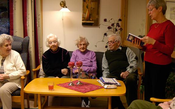 Foto som syner ei dame som les høgt frå ei bok for tre eldre kvinner og ein eldre mann. Dei set ved eit bord, medan ho som les, står ved enden av bordet. Foto: Leser søker bok