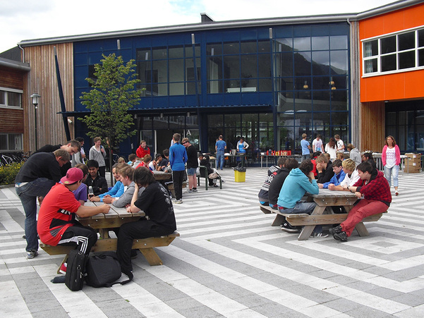 Utandørs foto av Stryn vidaregåande skule, elevar sit på benkar foran skulen, blå himmel, grønt gras.