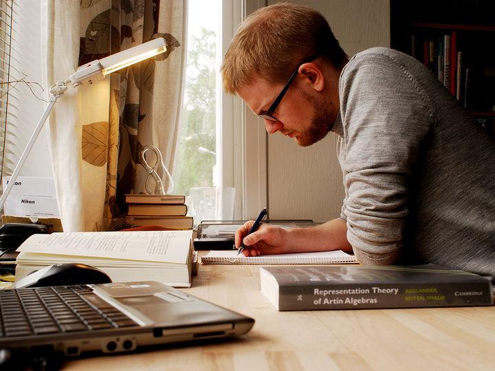 Foto som syner ein som sit og les til eksamen. Han sit bøygd over skrivepulten og har på seg grå gensar og briller. På bordet framfor seg har han fleire bøker, ei notatbok og ein pc. Foto: Stein Halvor Halvorsen, www.flickr.com