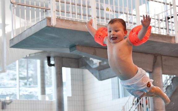 Foto som syner ein liten gut med oransje armringar og kvit badebukse i svevet frå eit av stupebrettet i badeanlegget i Trivselshagen på Sandane. Foto: Edvin-Andre Hugvik.