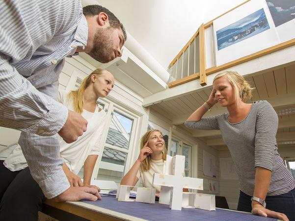 Foto som syner tre kvinner og ein mann rundt eit bord der dei har laga ein modell av noko i papp. Tre an dei ser engasjerte på den eine kvinna, som forklarer noko. Biletet skal illustrere gründerverksemd. Foto: Jo Bergersen