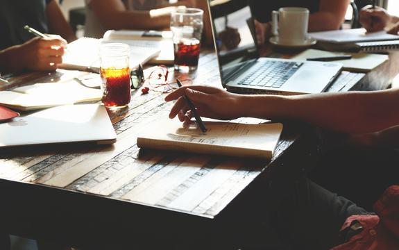 Bilete av hender som skriv, skriveblokker og datamaskiner