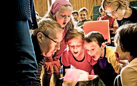 Foto som syner fem ungar og ein vaksen rundt noko som kanskje skal førestille eit bål. Biletet er frå eit arrangement i regi av Den kulturelle skulesekken og føregår inne i ein gymsal. I bakgrunnen ser vi fleire ungar. Foto: David Zadig