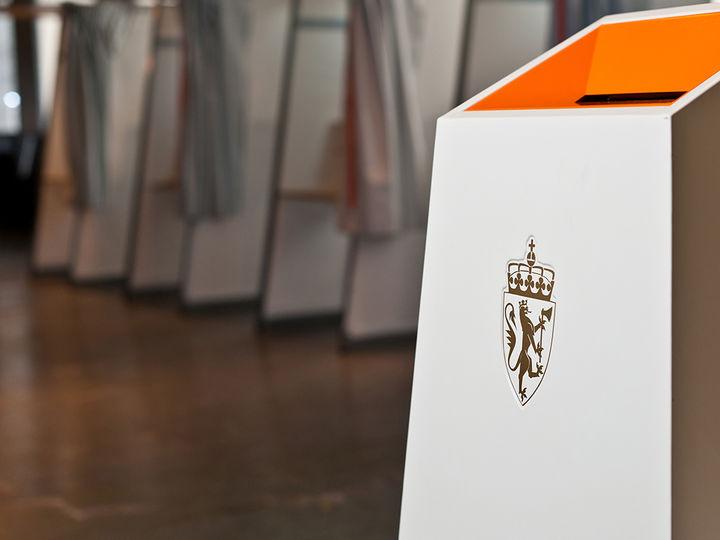 Foto frå eit stemmelokale, der vi ser den kvite og oransje stemmeurna med riksvåpenet i forkant. I bakgrunnen av biletet ser vi valavlukke med stemmesetlar. Foto: Kommunal og moderniseringsdepartementet