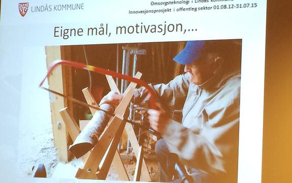 """Foto av presentasjon om Lindåsprosjektet, eit prosjekt om omsorgsteknologi i Lindås. Biletet syner ein eldre mann som sagar, med teksten """"Eigne mål, motivasjon""""."""