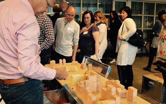Foto som syner deltakarar på konferansen Felles barn, felles ansvar i september 2015. Dei er samla rundt eit bord, der dei byggjer ein modell av ein by ved hjelp av treklossar.