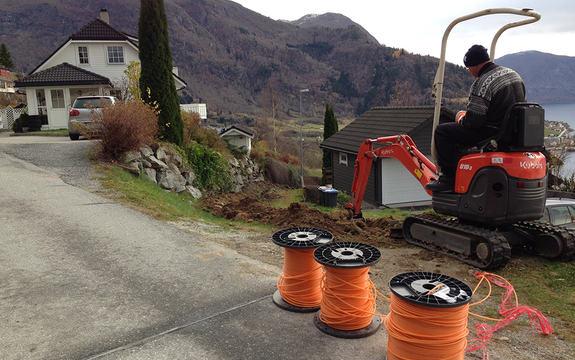 Foto som syner utbygging av breiband på Leikanger. Vi ser ein mann på ei lita gravemaskin og tre rullar med oransje kablar.