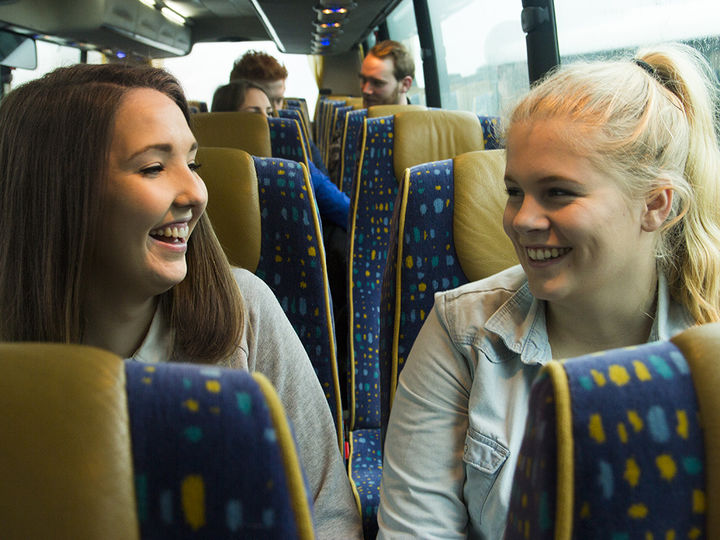 Foto som syner to jenter i ein buss. Dei sit på kvar si side av midtgangen, ei er mørkhåra, og den andre er blond. Foto: A til Å Grafisk Design og Media